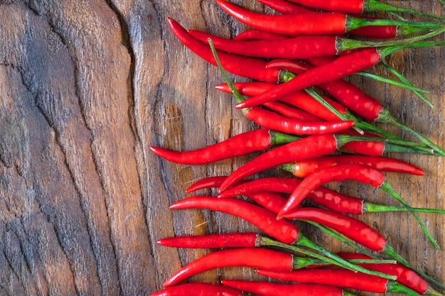 Peperoncini rossi freschi su un fondo di legno