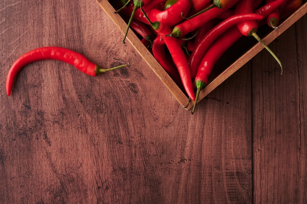 Peperoncini rossi in una scatola messa su una superficie di legno