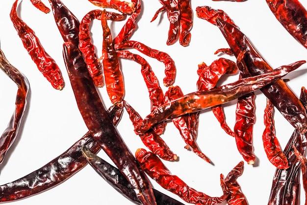 Peperoncini rossi secchi grandi e piccoli isolati su sfondo bianco