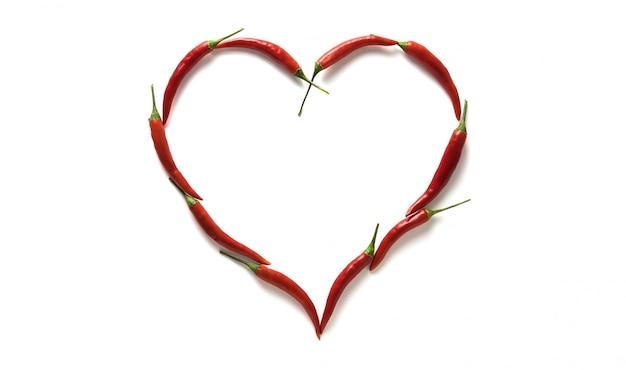 Peperoncini roventi sotto forma di un cuore isolato su fondo bianco