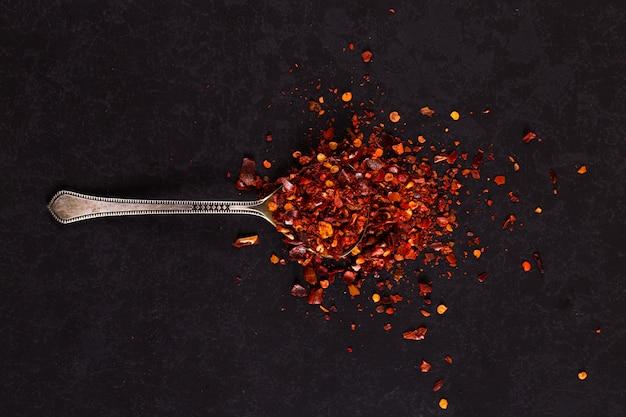 Peperoncini secchi schiacciati in un cucchiaio di ferro sparsi sul nero. , copyspace.