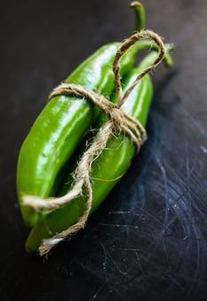 Peperoncini verdi del primo piano e tipi differenti di grani di pepe