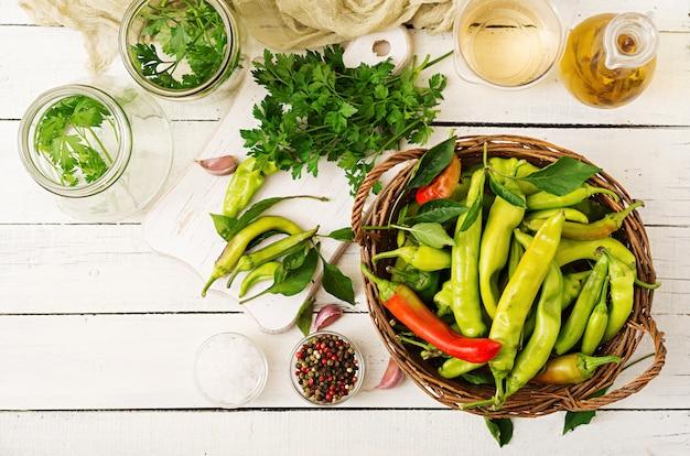Peperoncini verdi in un canestro su una tavola bianca.