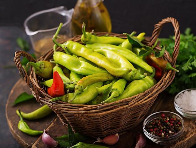 Peperoncini verdi in un canestro su una tavola scura