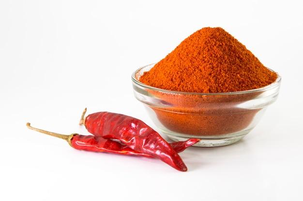 Peperoncino in polvere in una ciotola con peperoncini rossi secchi