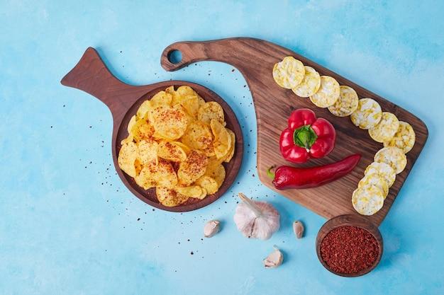 Peperoncino rosso e peperoni rossi affettati su un piatto di legno servito con le patatine fritte. foto di alta qualità