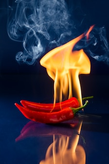 Peperoncino rosso fuoco, peperoncino, peperoncino, su una parete rossa e nera.