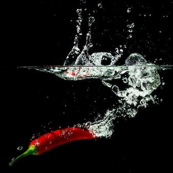 Peperoncino rosso rosso che spruzza nell'acqua contro fondo nero