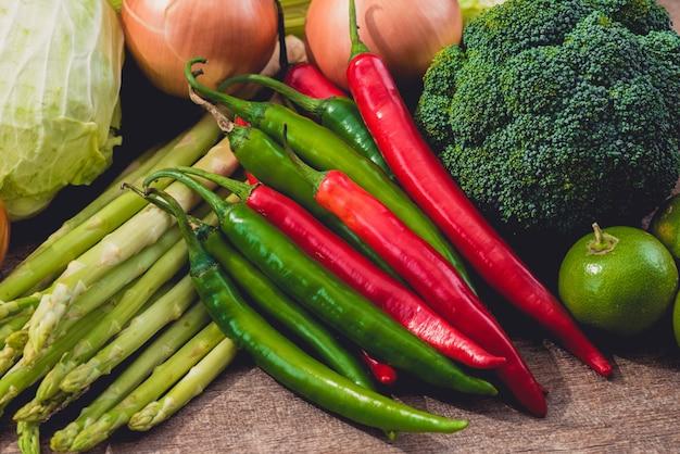 Peperoncino rosso rosso e verde e vari generi di verdure come fondo sulla tavola di legno