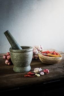 Peperoncino secco e cipolla rossa e aglio e pietra mortaio su un vecchio fondo di legno
