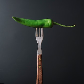 Peperoncino verde nella forcella sul contesto nero