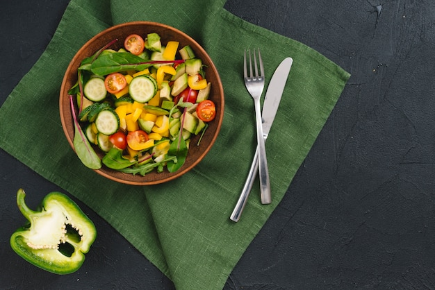 Peperone diviso in due e insalata di verdure miste sul tovagliolo verde sopra il contesto concreto nero