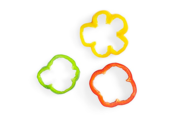 Peperone dolce dolce affettato tre colori su bianco isolato con il percorso di ritaglio.