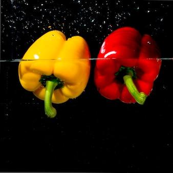 Peperone dolce rosso e giallo organico che galleggia sulla chiara acqua contro fondo nero