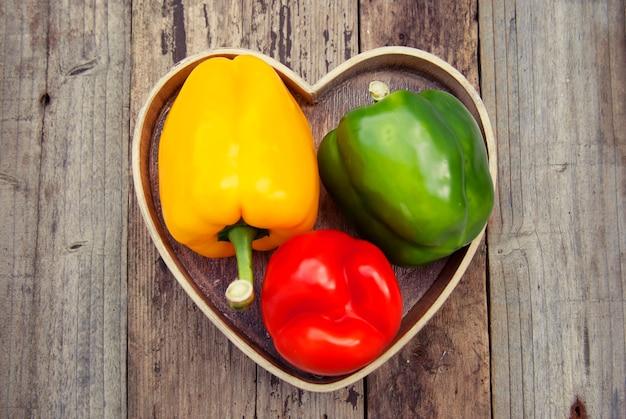 Peperone dolce verde, giallo e rosso sopra di legno strutturato rustico. verdure sane, cibo.