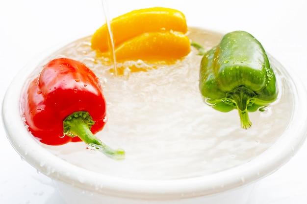 Peperone inzuppato d'acqua. lavare le verdure fresche su bianco