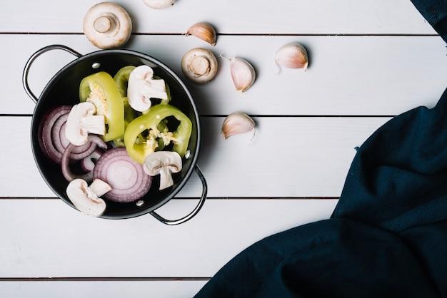Peperone verde a fette; funghi e cipolle in padella con spicchi d'aglio e tessile su superficie in legno