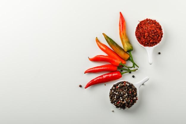 Peperoni colorati con grani di pepe e pepe di cayenna nella vista dall'alto di palette su uno sfondo bianco sfumato