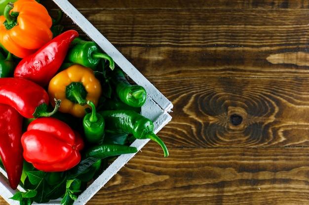 Peperoni colorati con le foglie in una scatola di legno su superficie di legno, disposizione piana.