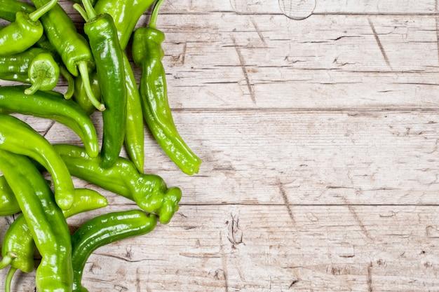 Peperoni crudi verdi freschi sul fondo di tavolo in legno rustico.