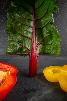 Peperoni dolci affettati peperone rosso e giallo maturo con foglia verde su sfondo grigio