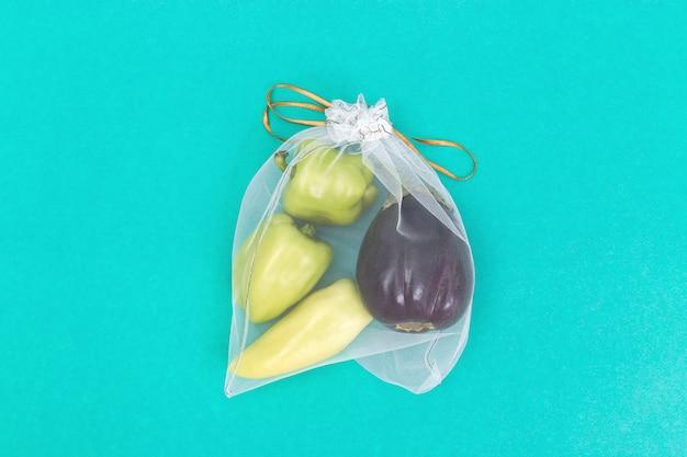 Peperoni dolci e melanzane verdi in borse naturali di eco che cucono dal panno della maglia sul fondo della carta della menta con lo spazio della copia. concetto di spesa alimentare zero sprechi. vista dall'alto