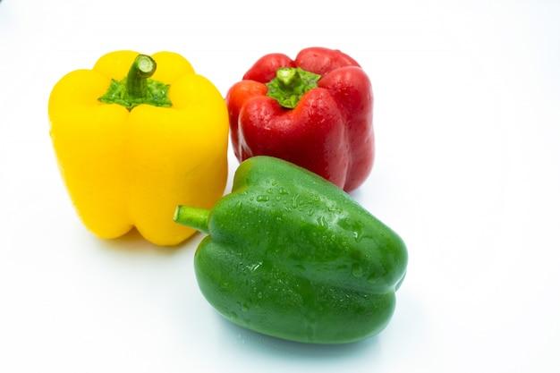 Peperoni dolci rossi, verdi e gialli su sfondo bianco