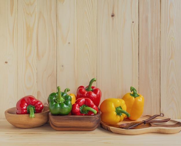 Peperoni dolci sul fondo della tavola in legno