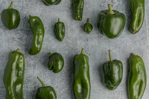 Peperoni dolci verdi su terra grigia