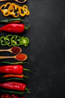 Peperoni e cucchiai di spezie sul tavolo nero