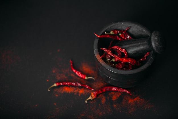 Peperoni e polvere piccanti rossi asciutti in mortaio di pietra sul nero.