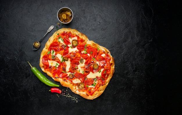 Peperoni fatti in casa pizza quadrata o pinza con mozzarella fusa, cipolla verde fresca e peperoncino su sfondo nero, vista dall'alto, piatto, spazio di copia