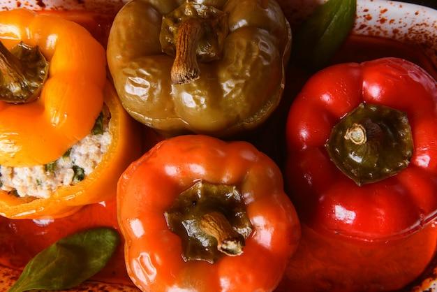 Peperoni fatti in casa, ripieni. con un ripieno di basilico, spinaci, formaggio e spezie. con sugo di pomodori freschi fatti in casa. realizzato in stile rustico.