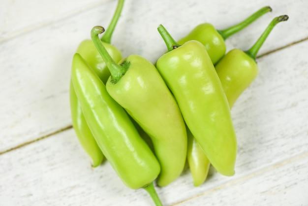 Peperoni freschi della banana o giardino verde del peperone dolce su un fondo di legno bianco - capsicum annuum