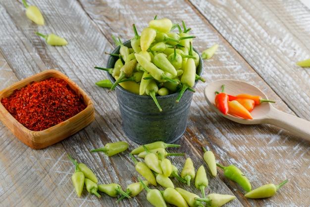 Peperoni in mini secchio e cucchiaio con la vista dell'angolo alto dei fiocchi del peperone su un di legno