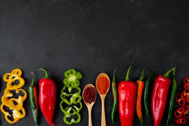 Peperoni interi e affettati con spezie sul tavolo nero