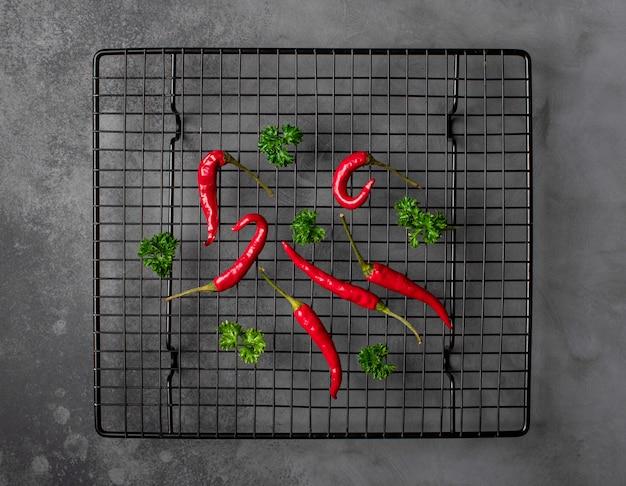 Peperoni organici freschi su una griglia del metallo. sfondo scuro. vista dall'alto