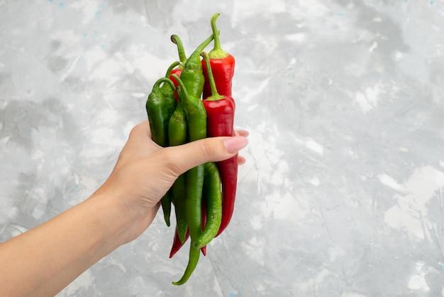 Peperoni piccanti colorati di vista superiore che tengono dal verde femminile e dal rosso su gray