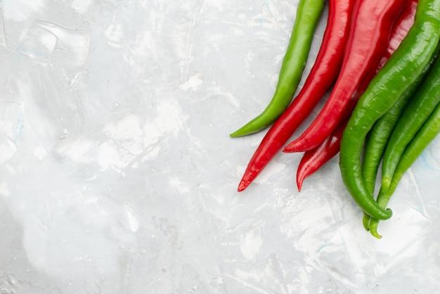 Peperoni piccanti colorati vista superiore verdi e rossi sullo scrittorio grigio