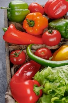 Peperoni, pomodori e pianta in un contenitore di legno. vista dall'alto.