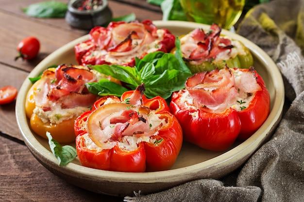 Peperoni ripieni con ricotta e pancetta in lamiera sul tavolo di legno. cibo balcanico.