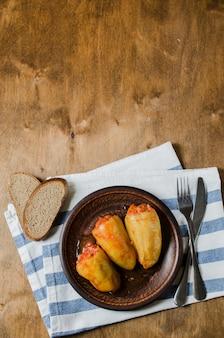 Peperoni ripieni con riso e carne macinata in umido in pomodori, pane di segale. cibo rustico