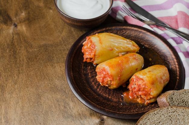 Peperoni ripieni con riso e spezzatino di carne macinata con pomodori, pane di segale. cibo rustico.