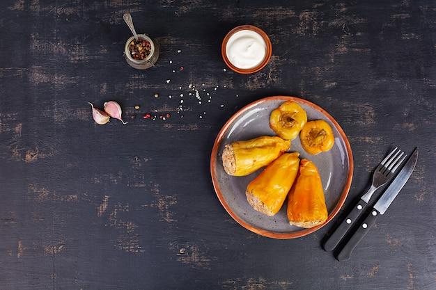 Peperoni ripieni variopinti con riso e carne tritata sulla tavola di legno. vista dall'alto.