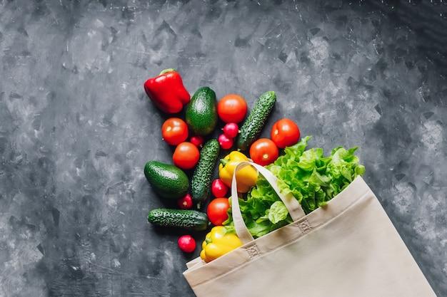 Peperoni rossi e gialli di verdure, cetrioli, pomodori, ravanelli, avocado, lattuga in un sacchetto di eco su uno sfondo scuro vista dall'alto