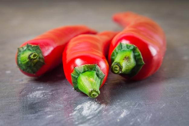 Peperoni rossi freschi isolati su sfondo grigio.