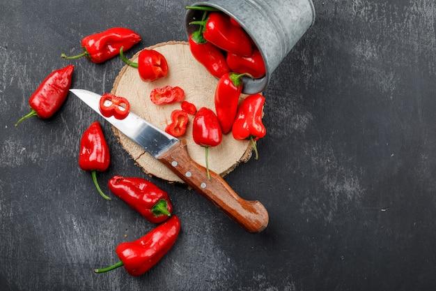 Peperoni sparsi con pezzo di legno, coltello in un mini secchio sul muro grigio sgangherata, piatto laici.