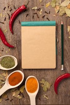 Peperoni, spezie in cucchiai, quaderno e matita