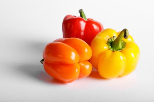 Peperoni tricolori isolati su bianco
