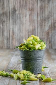 Peperoni verdi in una vista laterale del mini secchio su un di legno